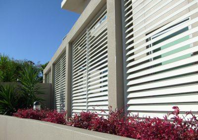 brise-soleil-orientable-installe-sur-brise-vue-le-long-d-un-immeuble