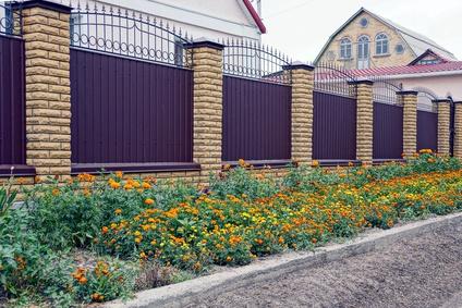 серо коричневый забор и ворота возле цветочной клумбы