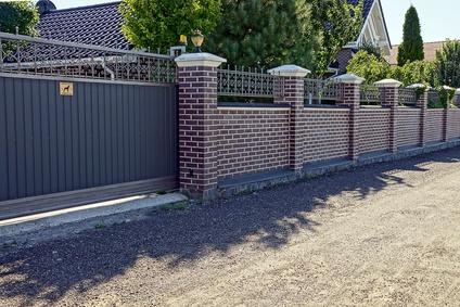 Серые железные ворота и кирпичный забор перед дорогой